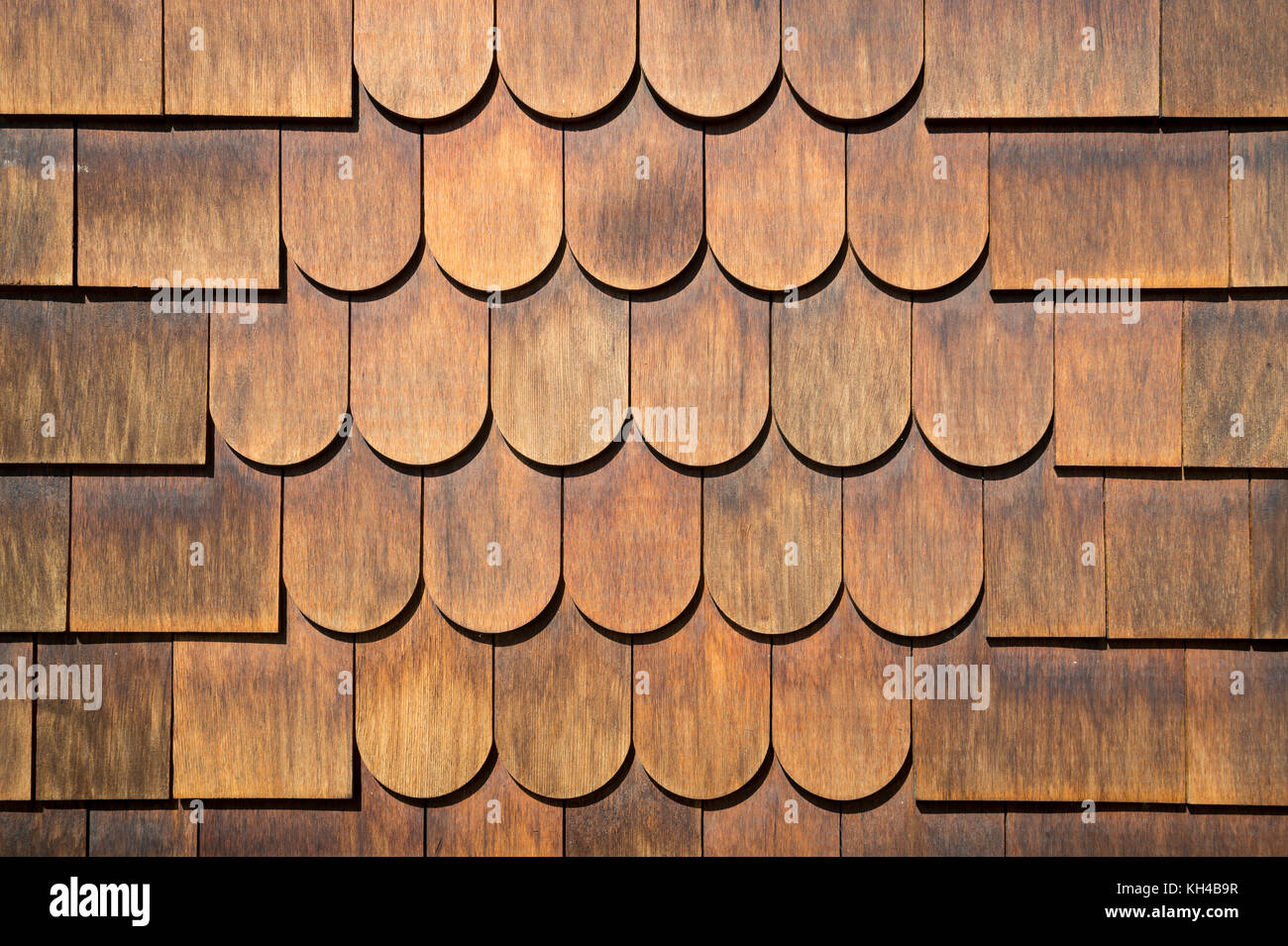Abstract close-up view of classic half-rounded cedar shingle siding. - Stock Image