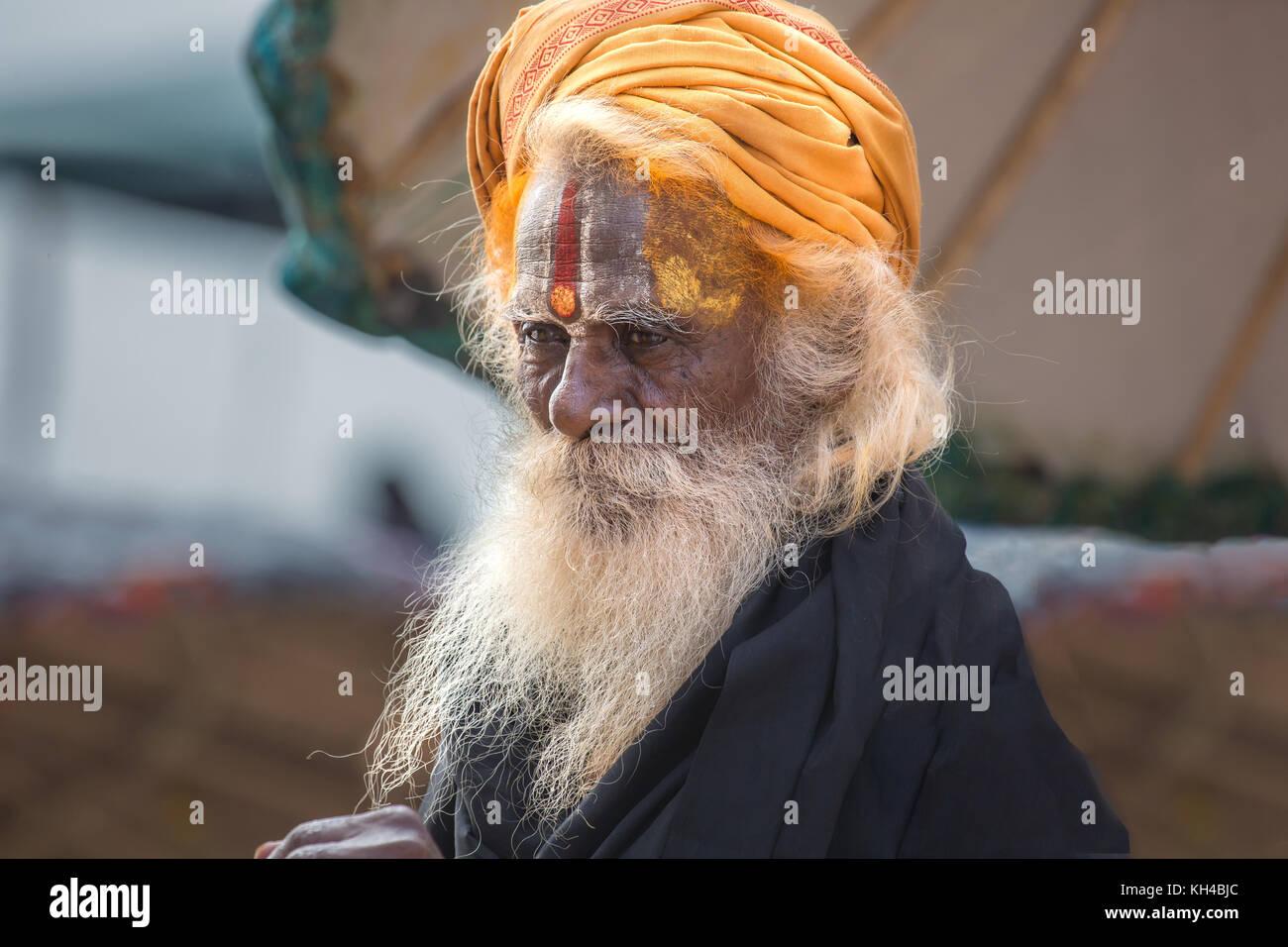 Portrait of Hindu sadhu, holy man on the Ganges river ghat at Varanasi India - Stock Image
