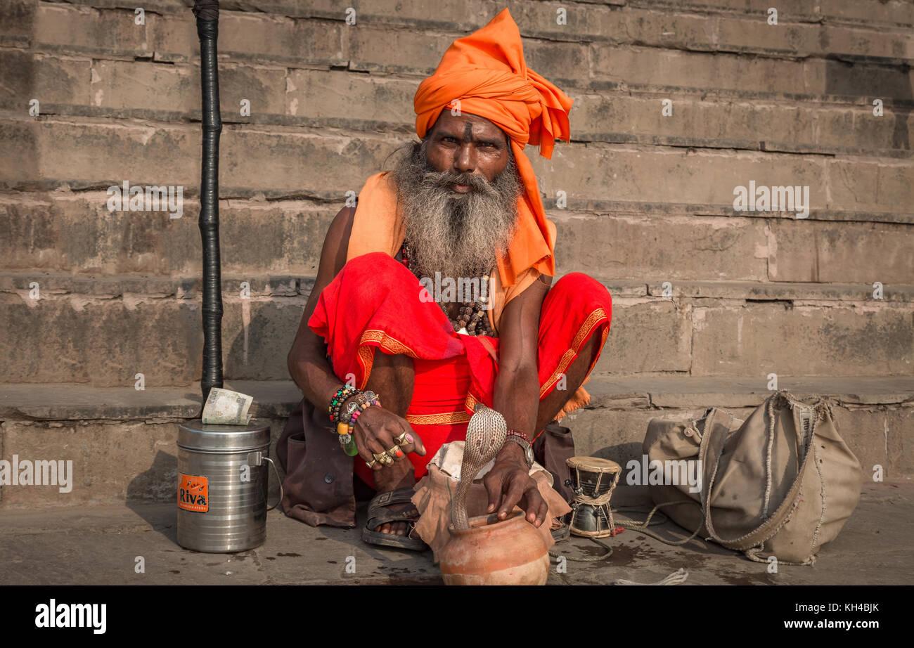 Holy sadhu man with his pet snake at the Ganga river bank at Varanasi, India. - Stock Image