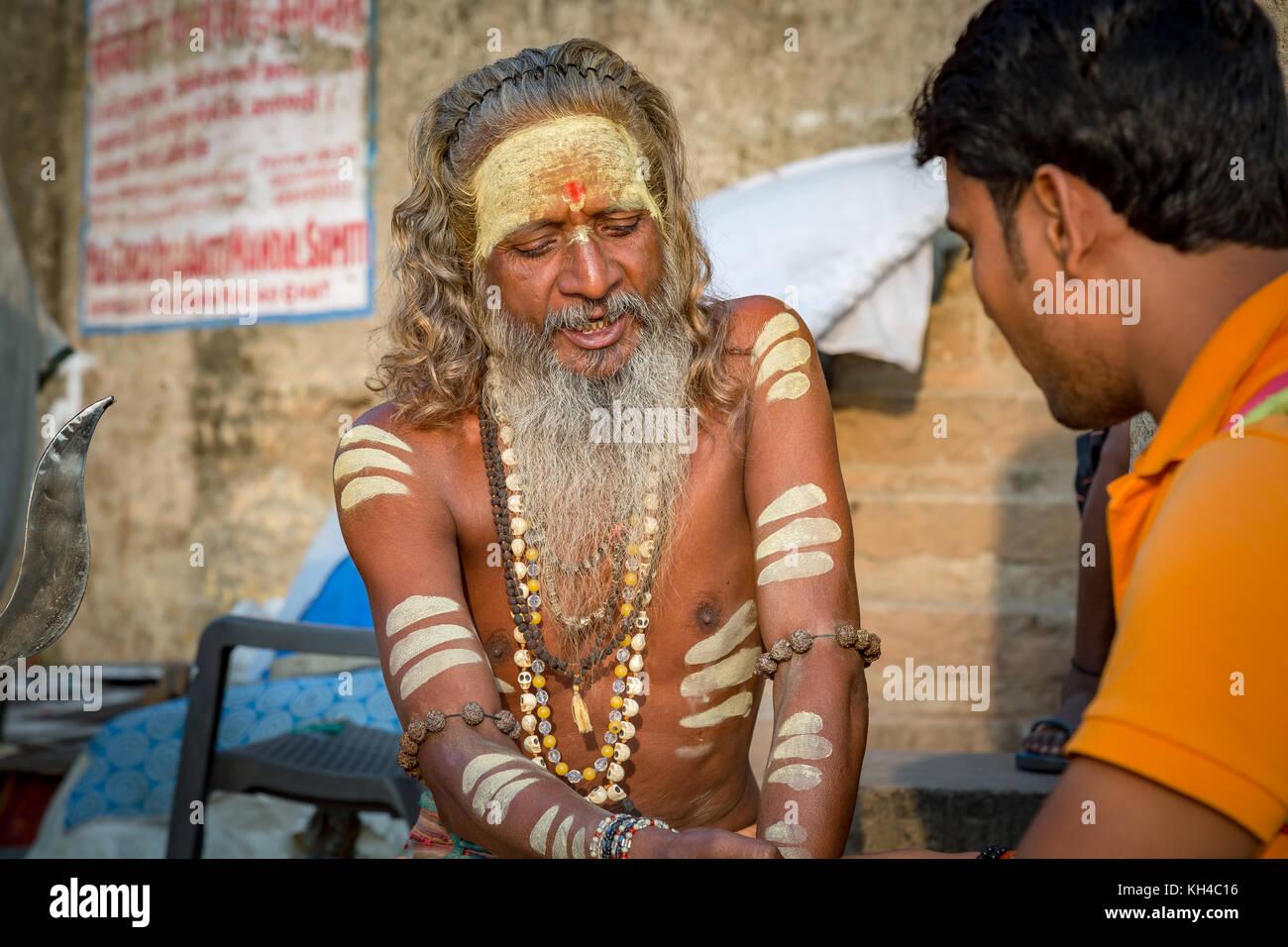 Varanasi sadhu man preaching a youth at the Ganges river bank Varanasi India - Stock Image