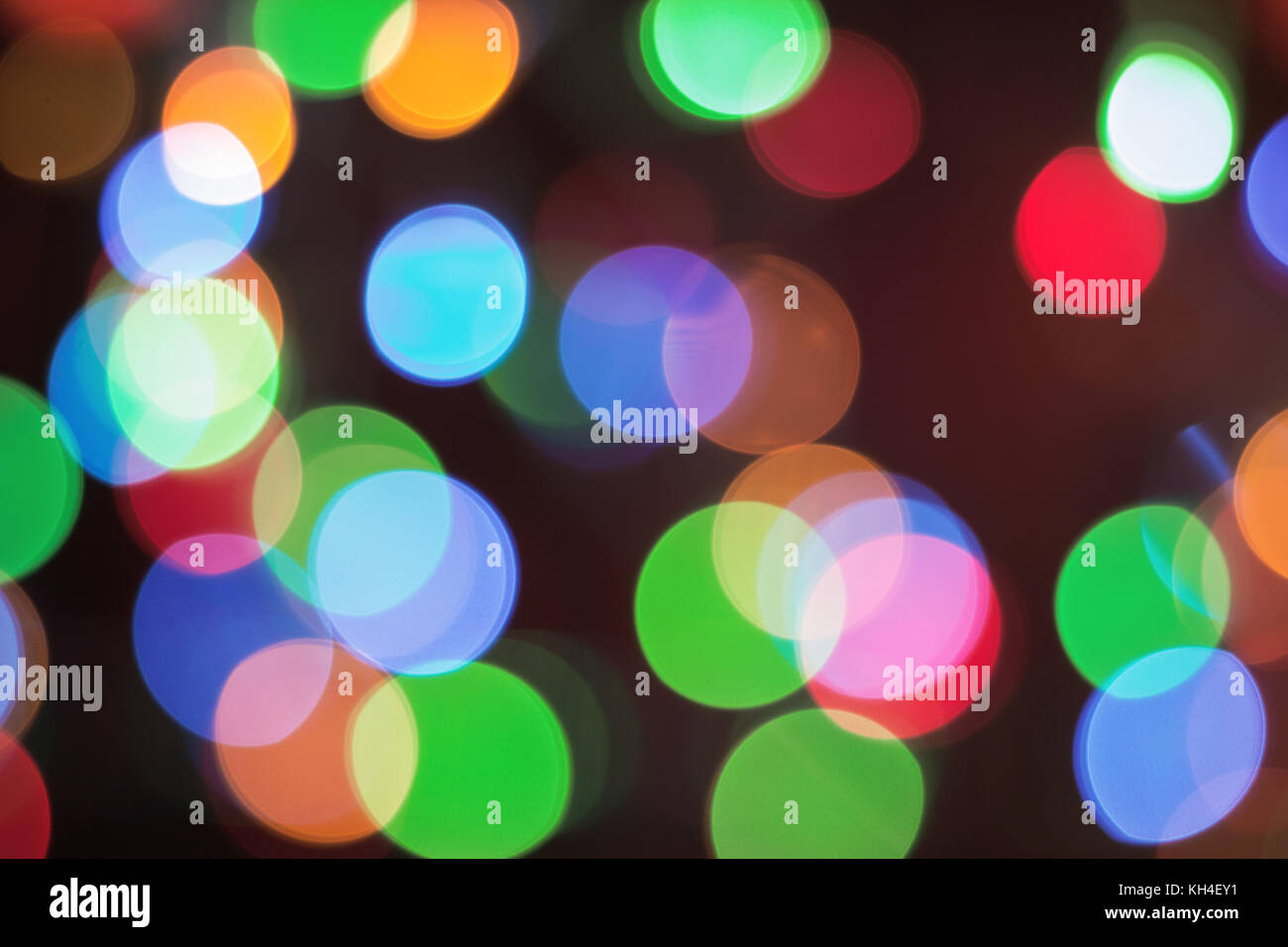 Color light blurred background, green, blue, red and yellow lights unfocused. Christmas decorations, garland illumination - Stock Image