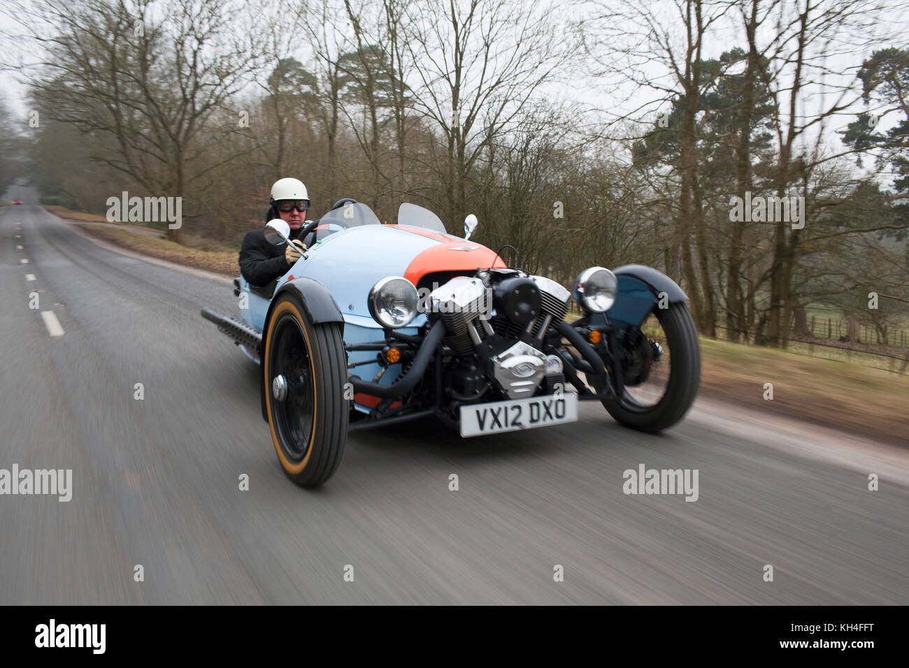 A Morgan three wheeler being driven through the British countryside. - Stock Image