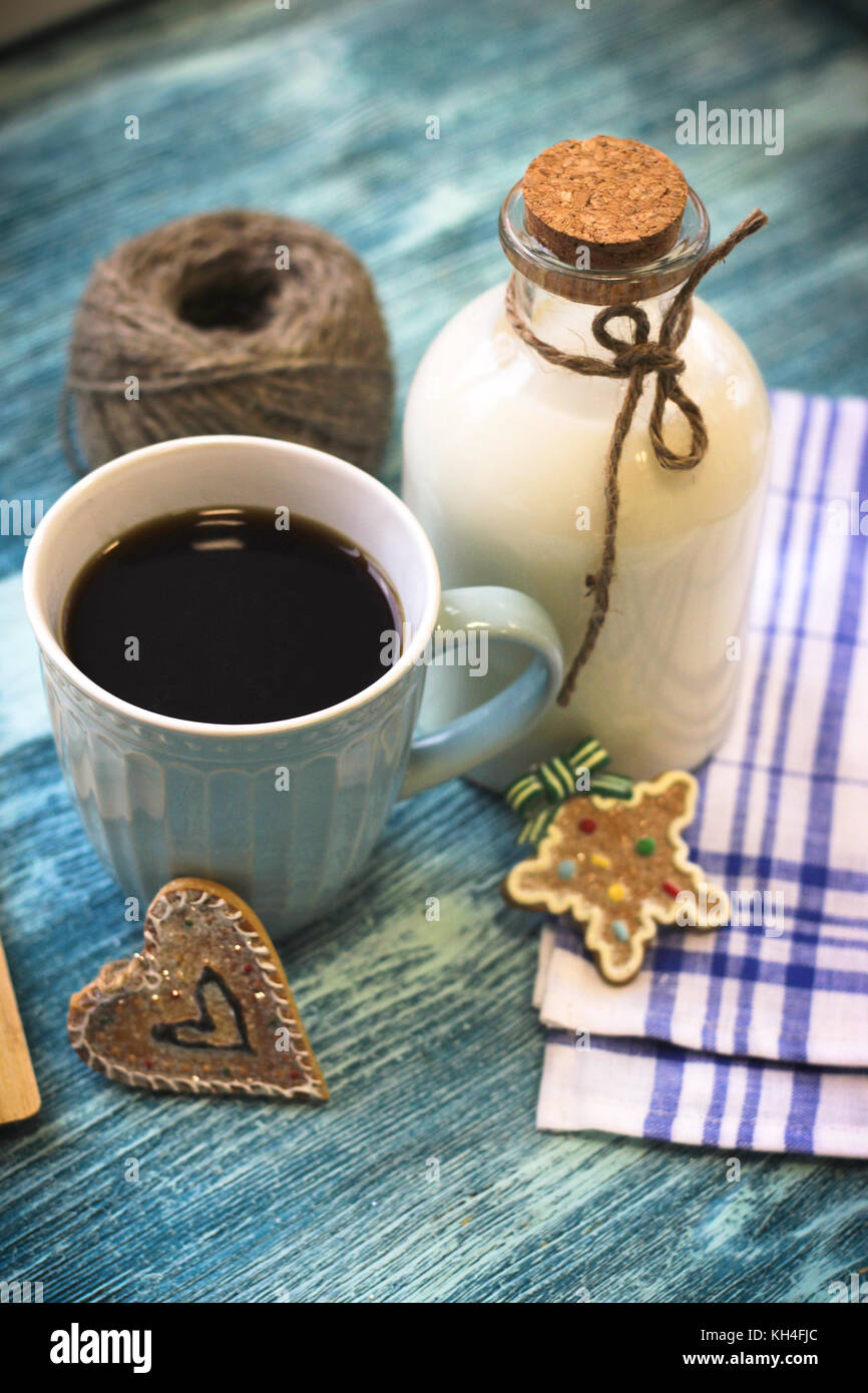 Festive still life with a bottle, a cup, biscuits - Stock Image