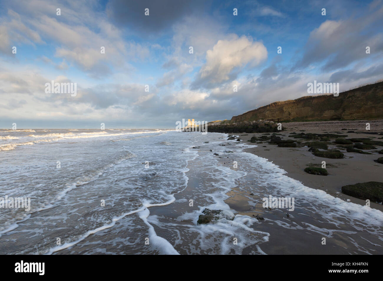 Big clouds and soft waves at Reculver beach on the north Kent coast, UK. - Stock Image