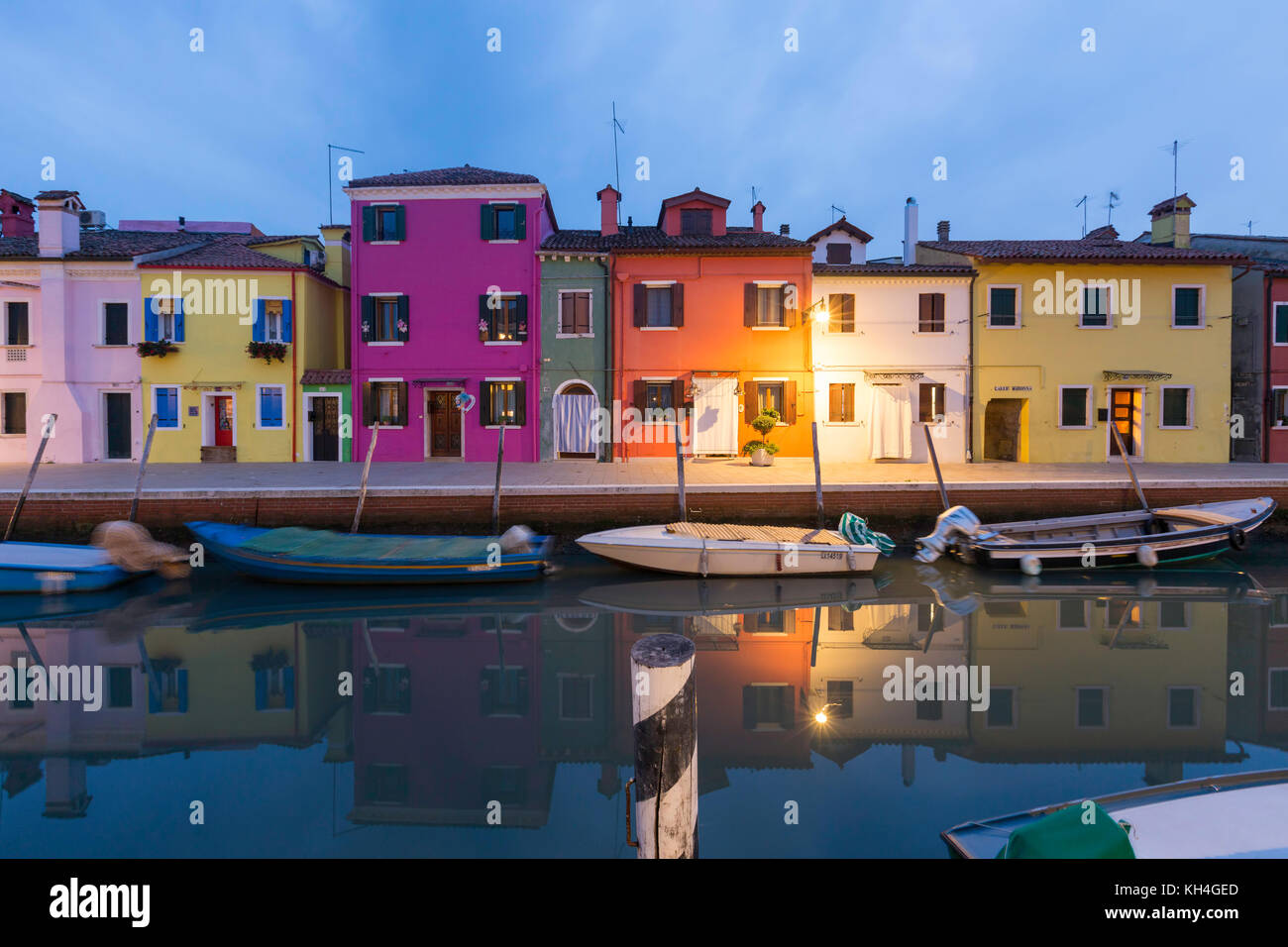 Fishermen's houses and small fishing boats reflected in the canal on Fondamenta della Pescheria, Burano in the Venetian Stock Photo