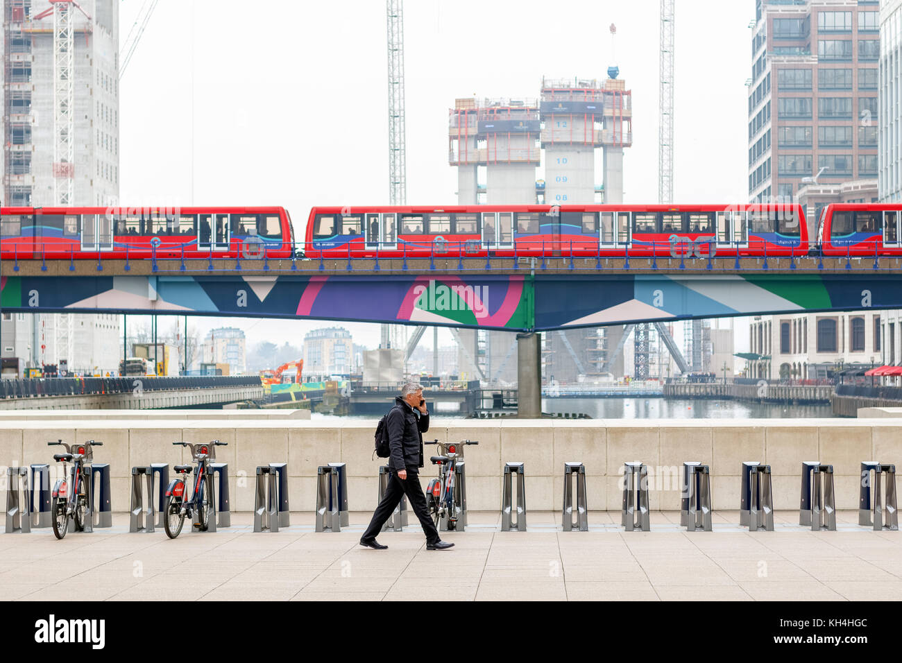 London, UK - November 24, 2017 - A businessman walking on Reuters Plaza in Canary Wharf with DLR trains passing Stock Photo