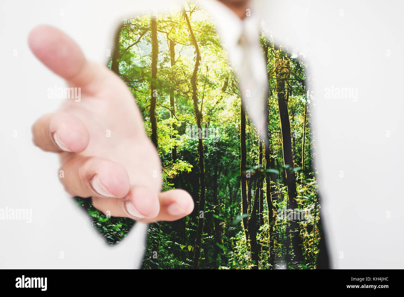 Double exposure, Businessman stretching hand to hand shake with Green trees in the forest. Eco friendly and sustainable - Stock Image
