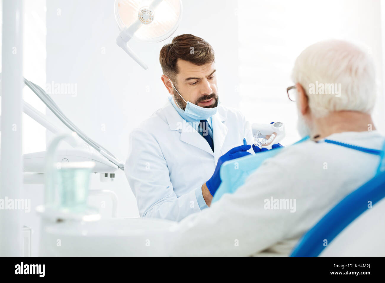 Attentive stomatologist holding false teeth in hands - Stock Image