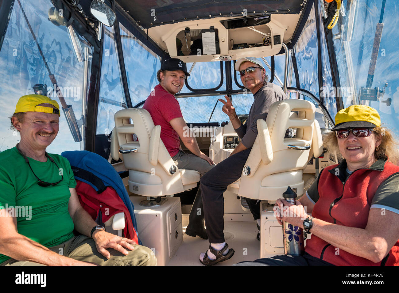 Four people sitting in a  speedboat, returning from a fishing trip, smiling, looking at camera, Vancouver Island - Stock Image