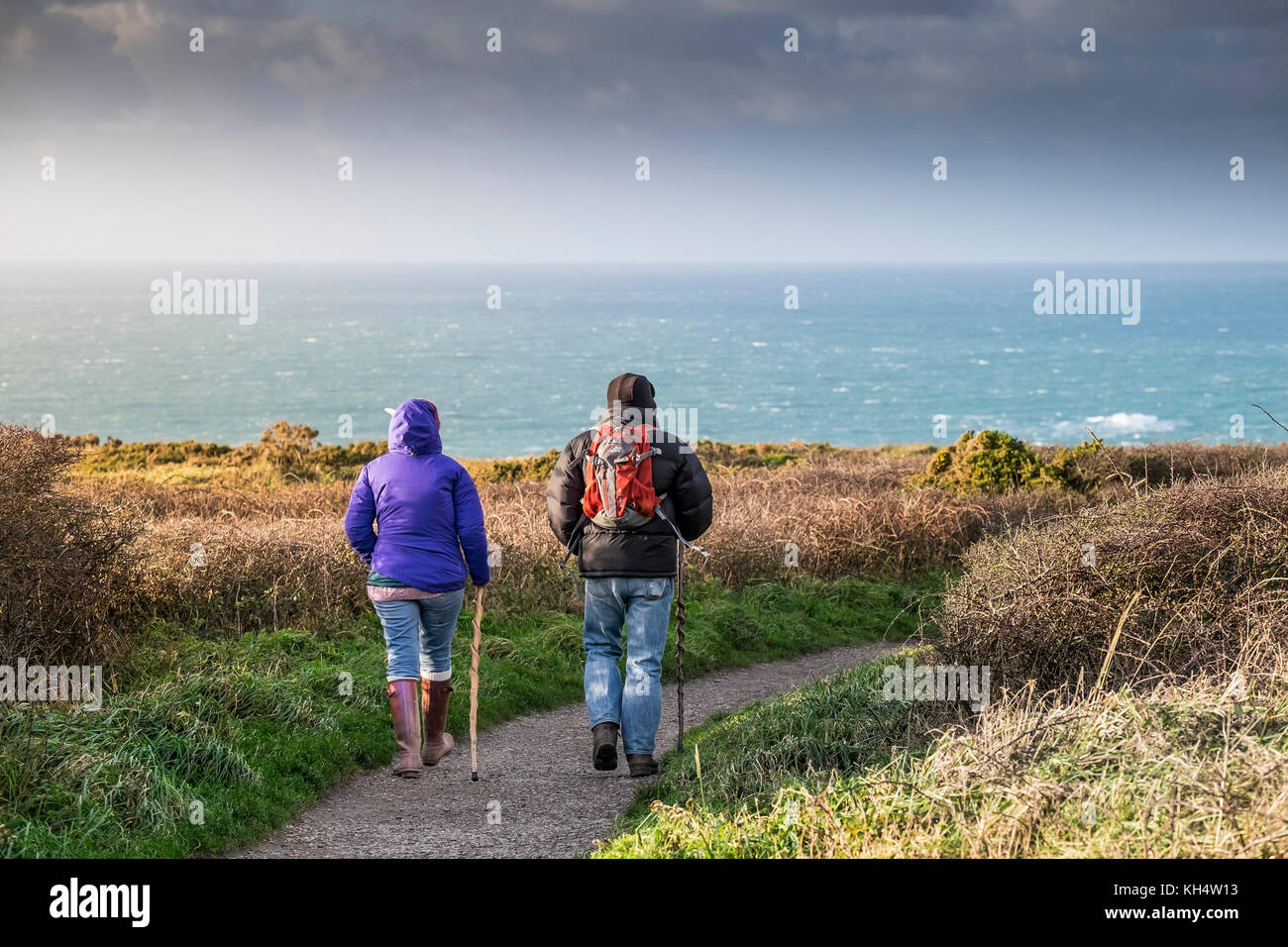 Two walkers people couple walking on a footpath at Beduthan in Cornwall UK. - Stock Image