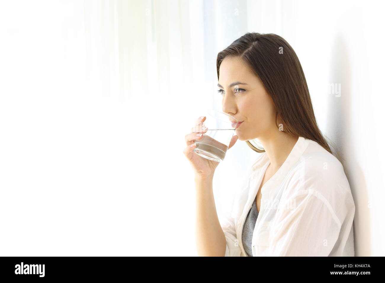 Portrait of a happy woman drinking water from a glass isolated on white at side - Stock Image