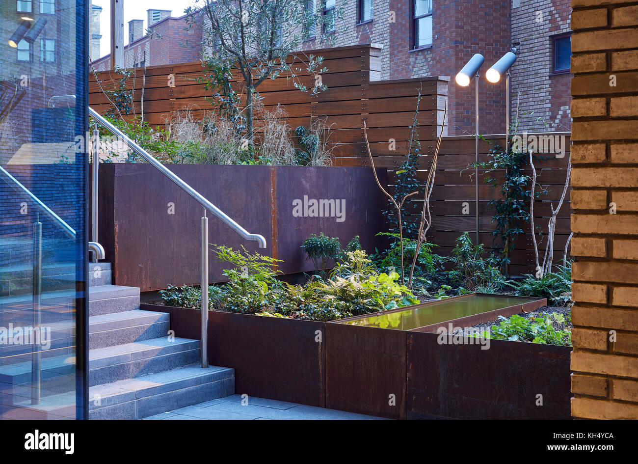 landscaped garden with outdoor lighting and raised metal garden beds