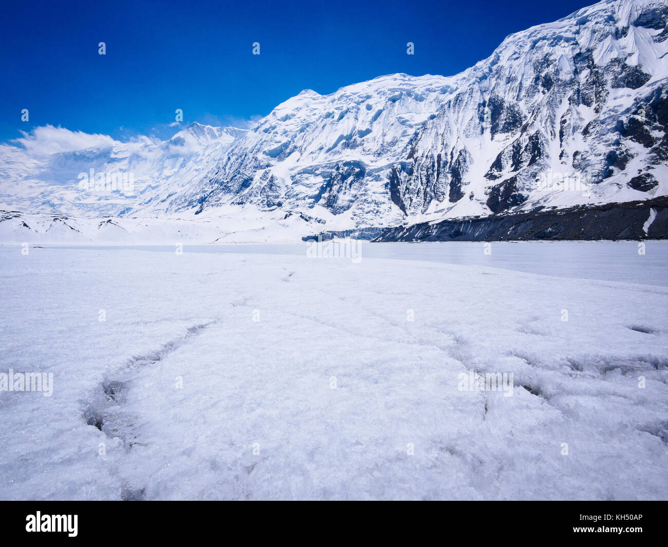Snowy shore of Tilicho Lake in the Annapurna Himalayas, Nepal - Stock Image