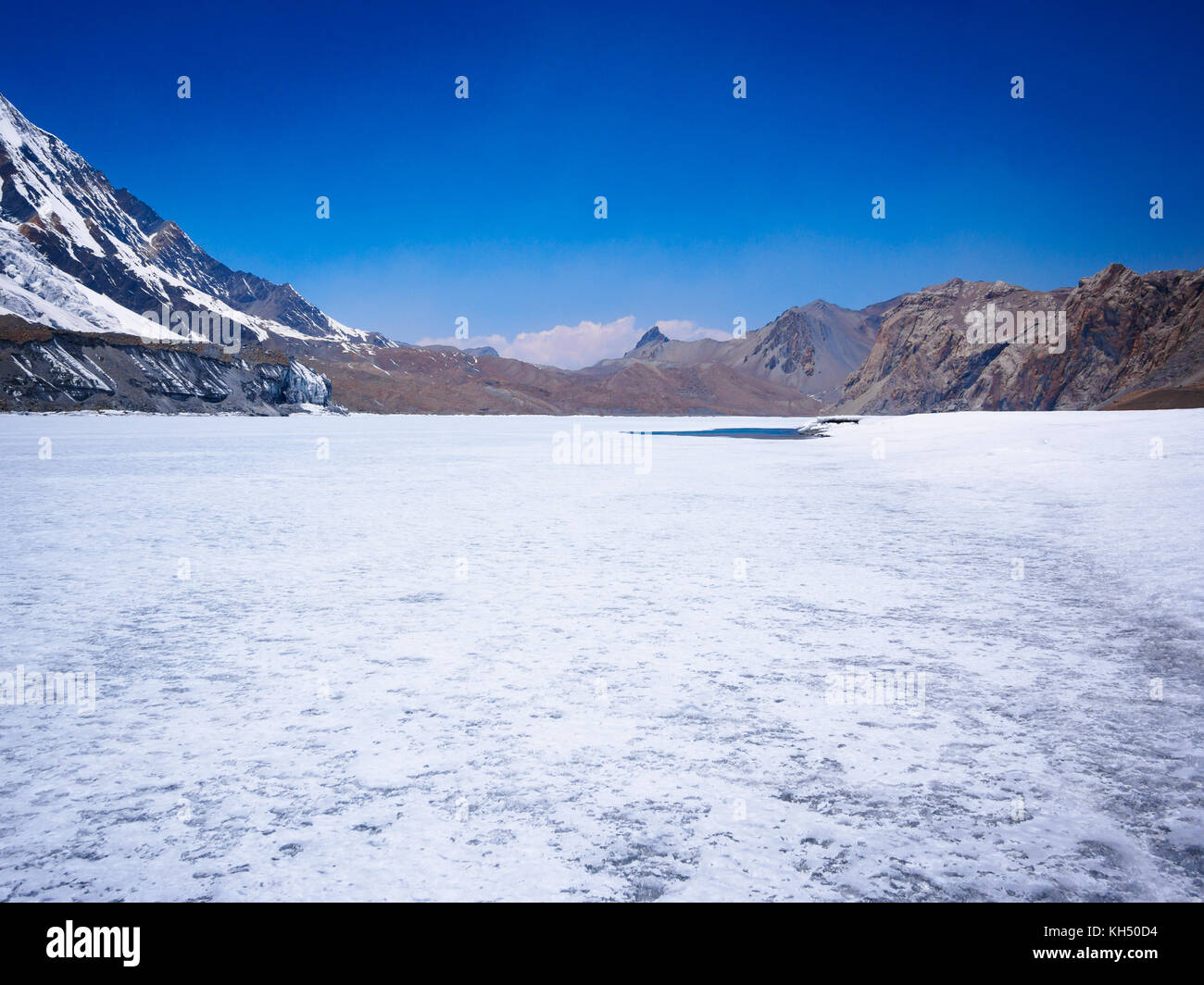 White frozen expanse of Tilicho Lake in the Annapurna Himalayas, Nepal - Stock Image