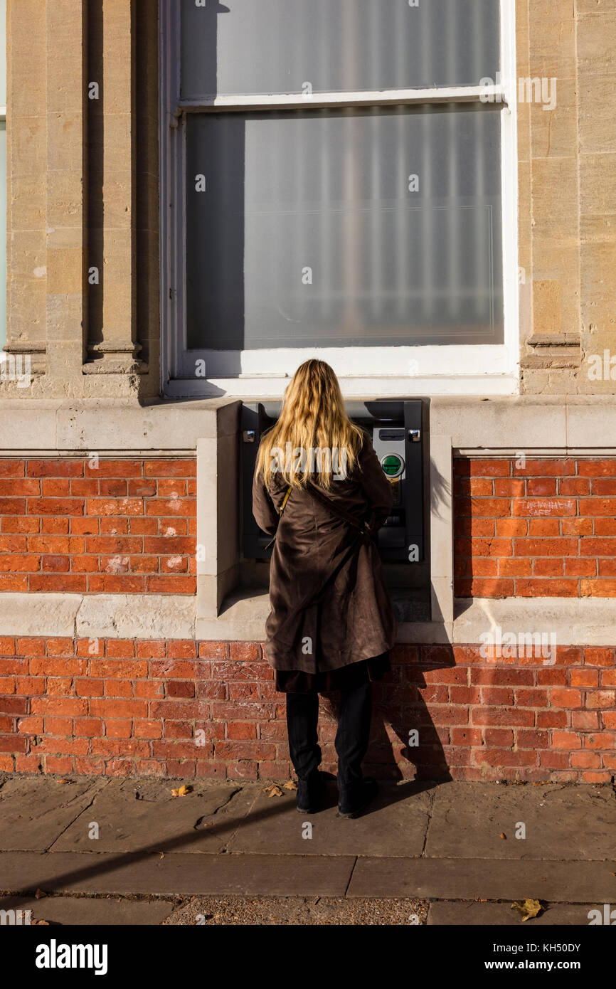 A blonde woman uses a cash machine outside of the NatWest bank on the High Street in Tenderden, Kent, UK - Stock Image