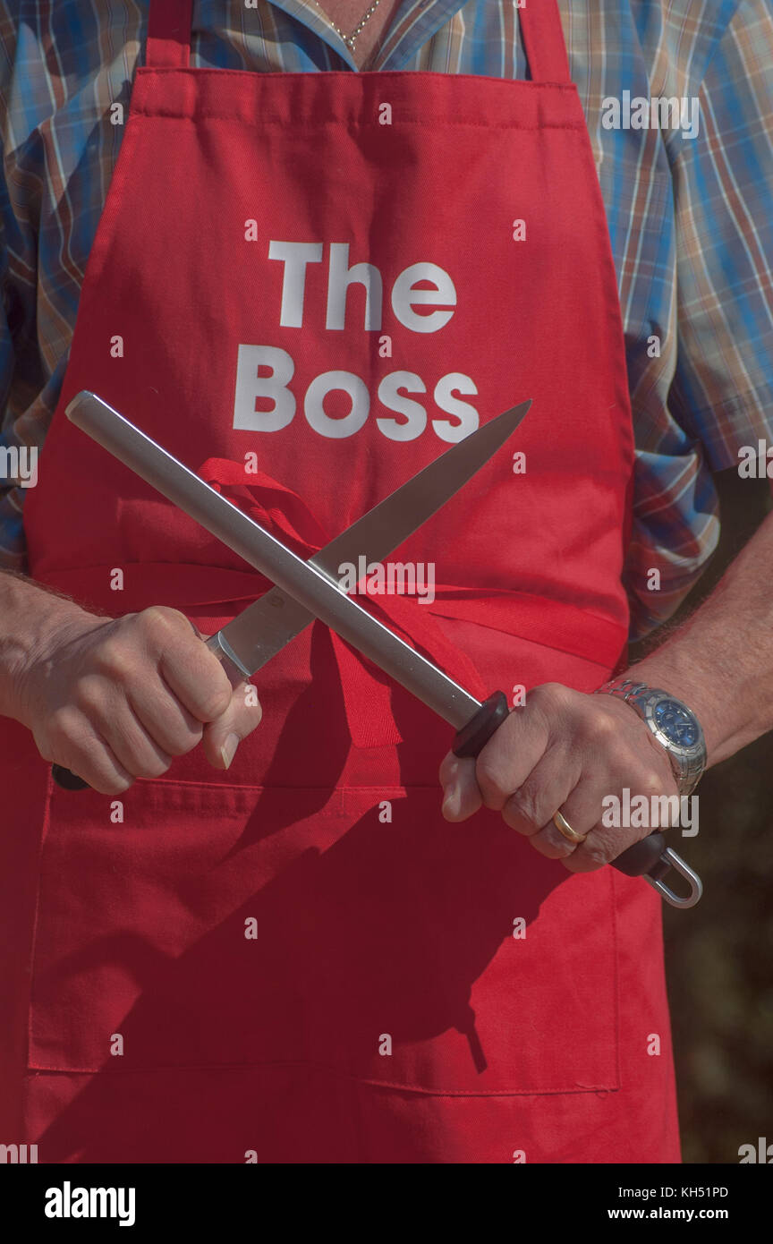 Man wearing 'The Boss' apron sharpening knife with a steel - Stock Image