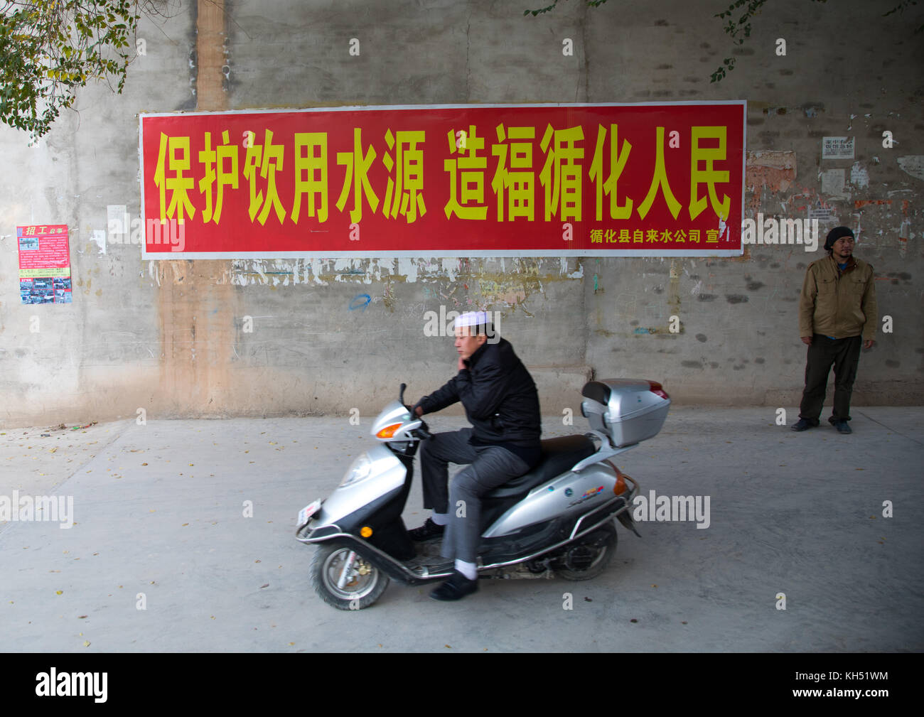 Salar ethnic minority man on a scooter passing in front of a chinese propaganda poster about saving water, Qinghai - Stock Image