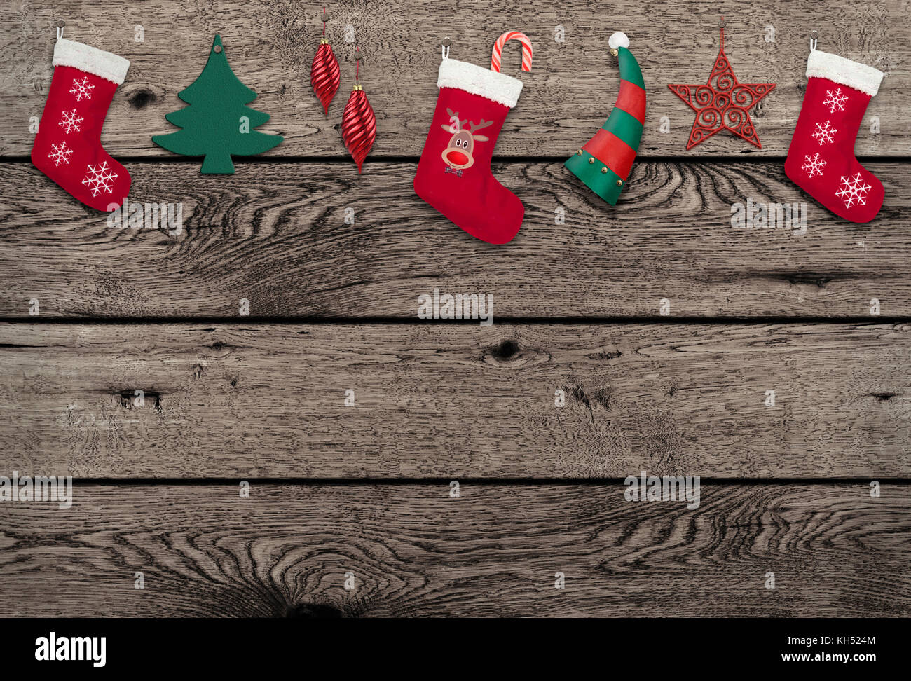 vintage weathered wooden background with cute hanging Christmas elements - Stock Image