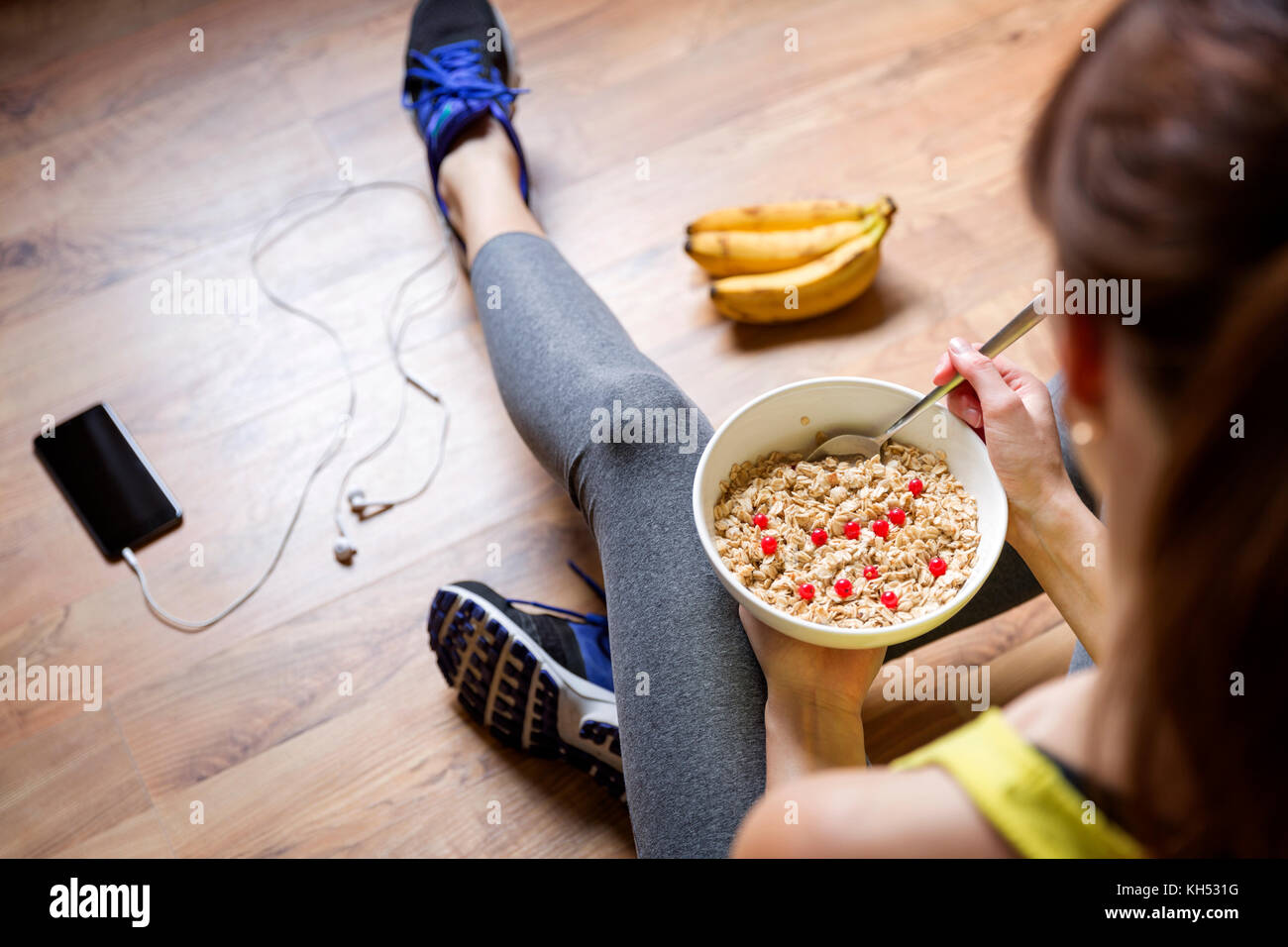 Young girl eating a oatmeal with berries after a workout . Fitness and healthy lifestyle concept. - Stock Image