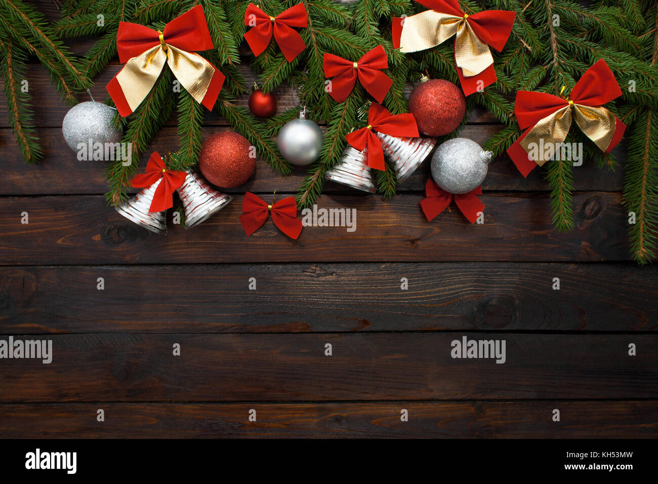 Green living spruce branches on a dark wooden background. New Year background with beautiful balls and red bows - Stock Image