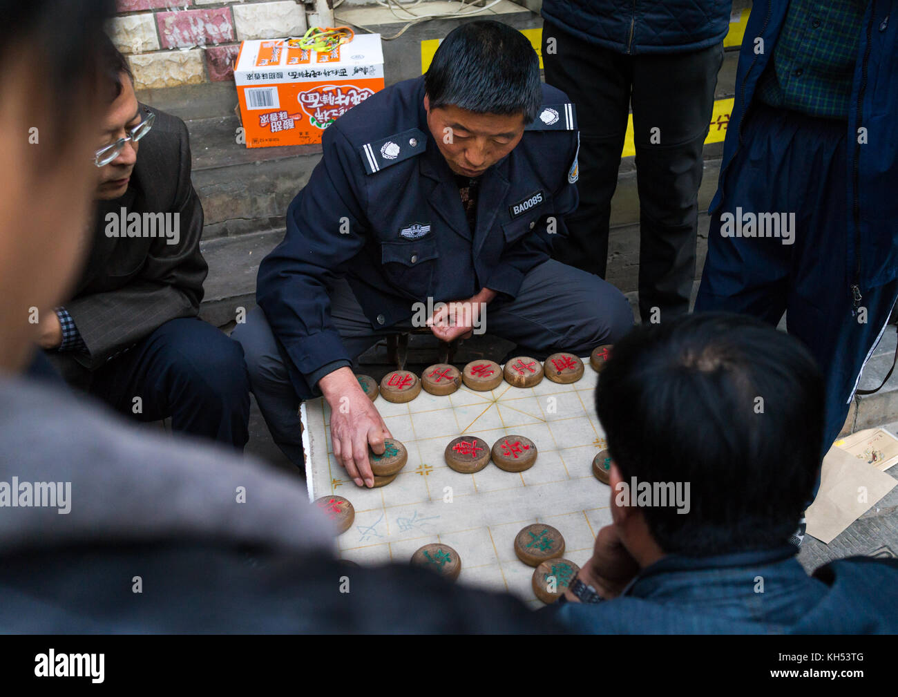 Group of people playing mah-jong in the street, Gansu province, Lanzhou, China - Stock Image