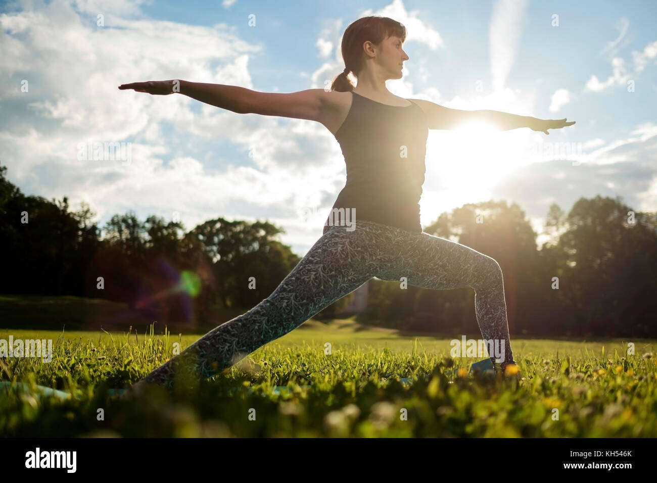 Beautiful young caucasian woman practices yoga asana Virabhadrasana 1 - Stock Image