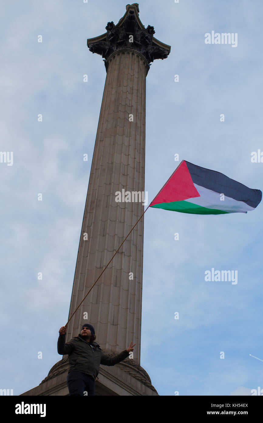 A protestor waves the Palestinian flag under Nelson's Column on the centenary of the Balfour Declaration,  Trafalgar - Stock Image