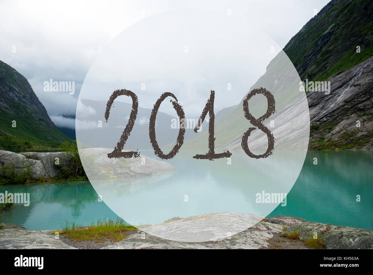 text 2018 for happy new year greetings lake with mountains in norway cloudy sky peaceful scenery landscape with rocks and grass greeting card