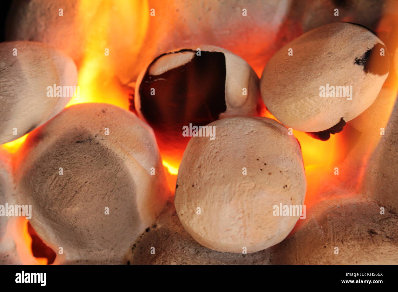Close up of gas fire coals with yellow orange flames, glowing orange, and with soot on two of coals. - Stock Image