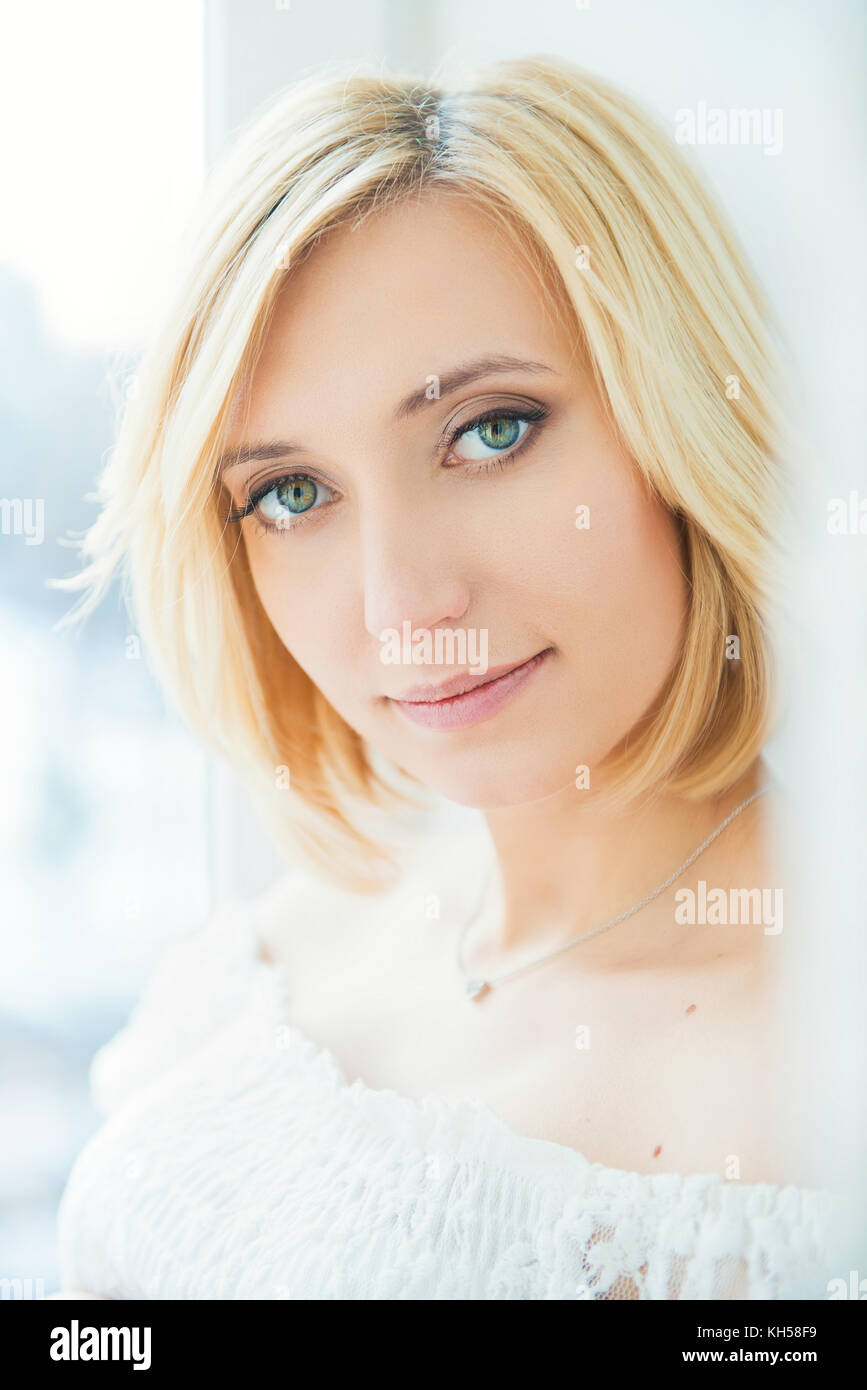 Portrait of a young blonde woman with blue eyes - Stock Image