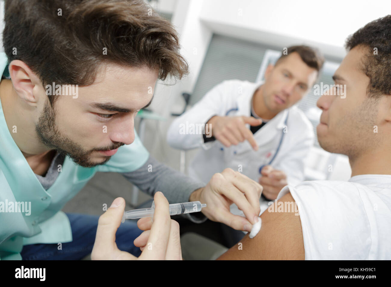 young doctor doing injured man tetanus toxoid injection - Stock Image