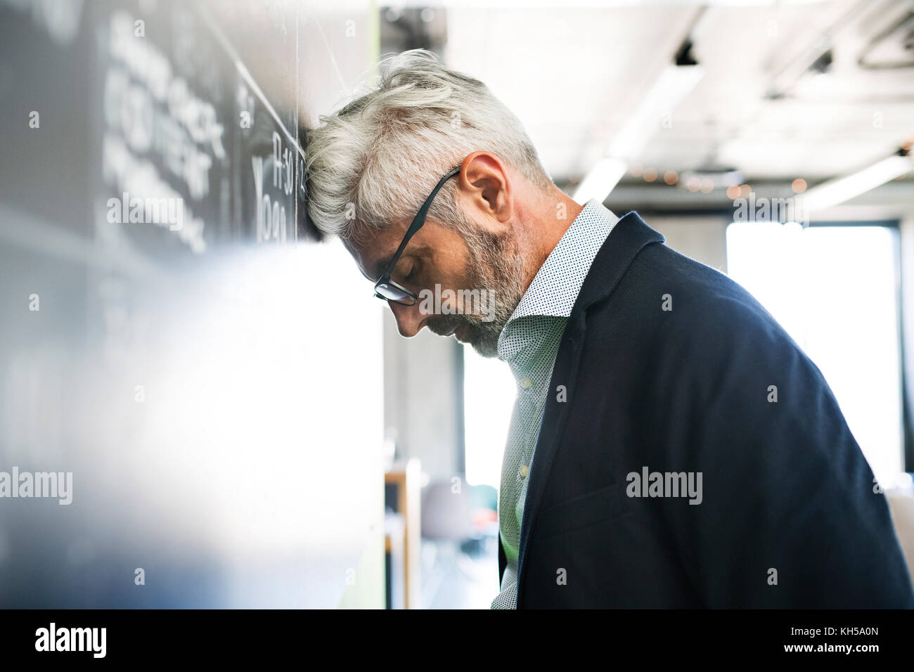 Worried mature businessman in the office. - Stock Image
