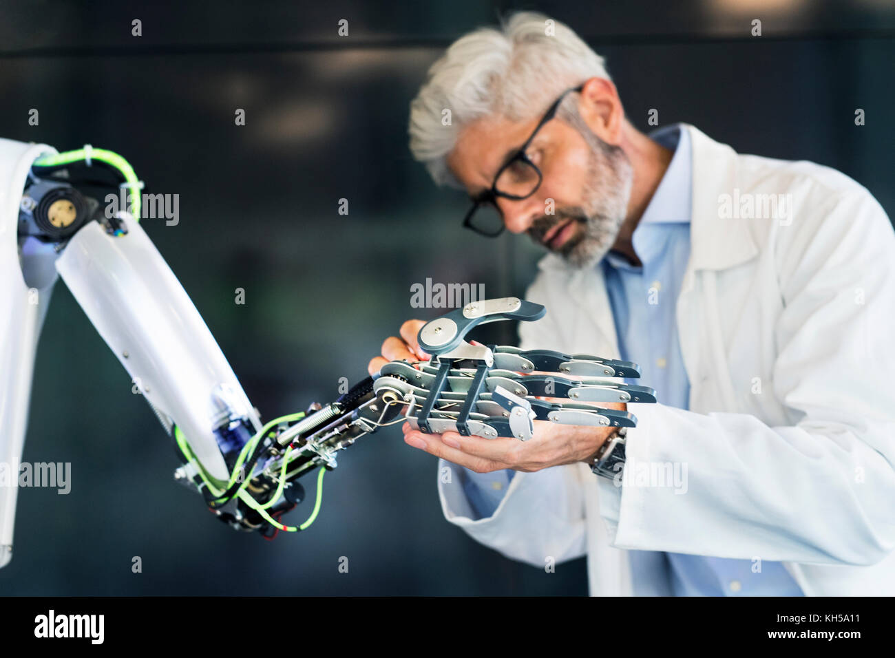 Mature businessman or scientist with a robot. - Stock Image