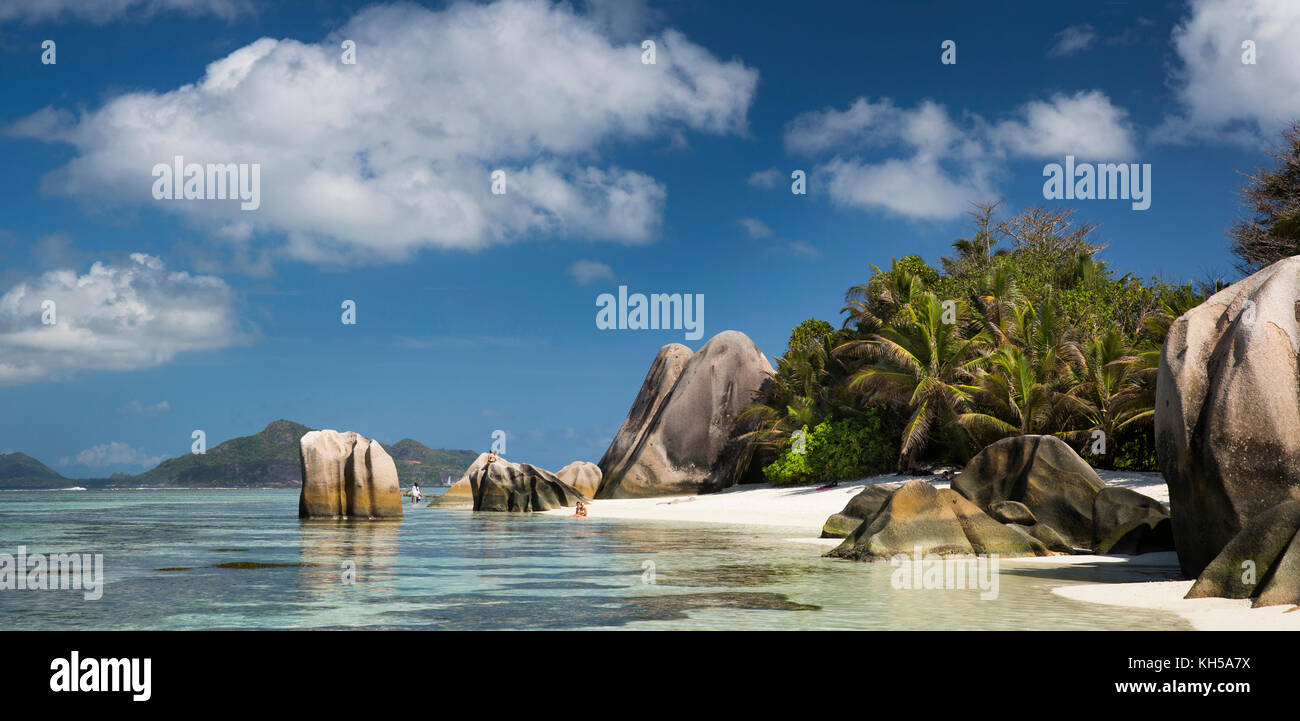 The Seychelles, La Digue, L'Union Estate, tourists in sea at Anse Source d'Argent beach, panoramic - Stock Image