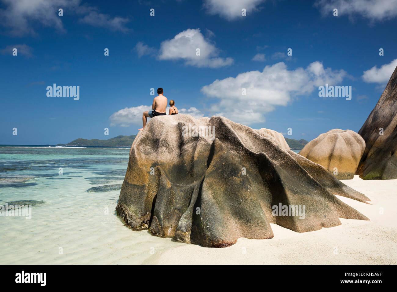 The Seychelles, La Digue, L'Union Estate, tourists sat on rocks at Anse Source d'Argent beach - Stock Image