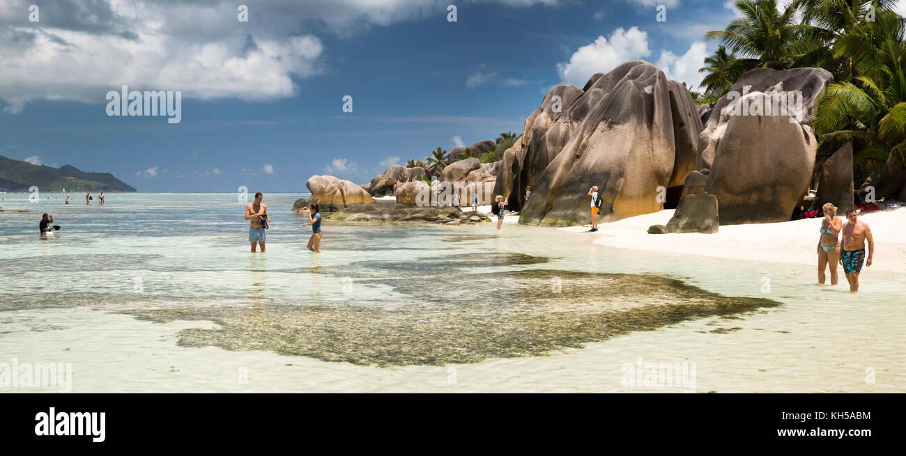 The Seychelles, La Digue, L'Union Estate, tourists on Anse Source d'Argent beach, panoramic - Stock Image