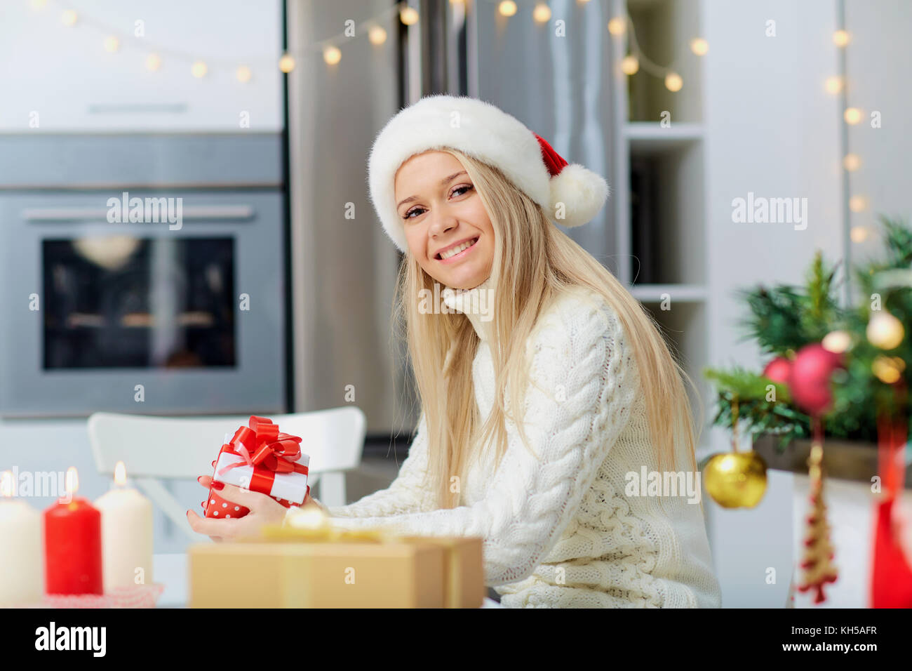 c45a9cb80328b A blonde girl in a Santa Claus hat with a gift in her hand for C ...