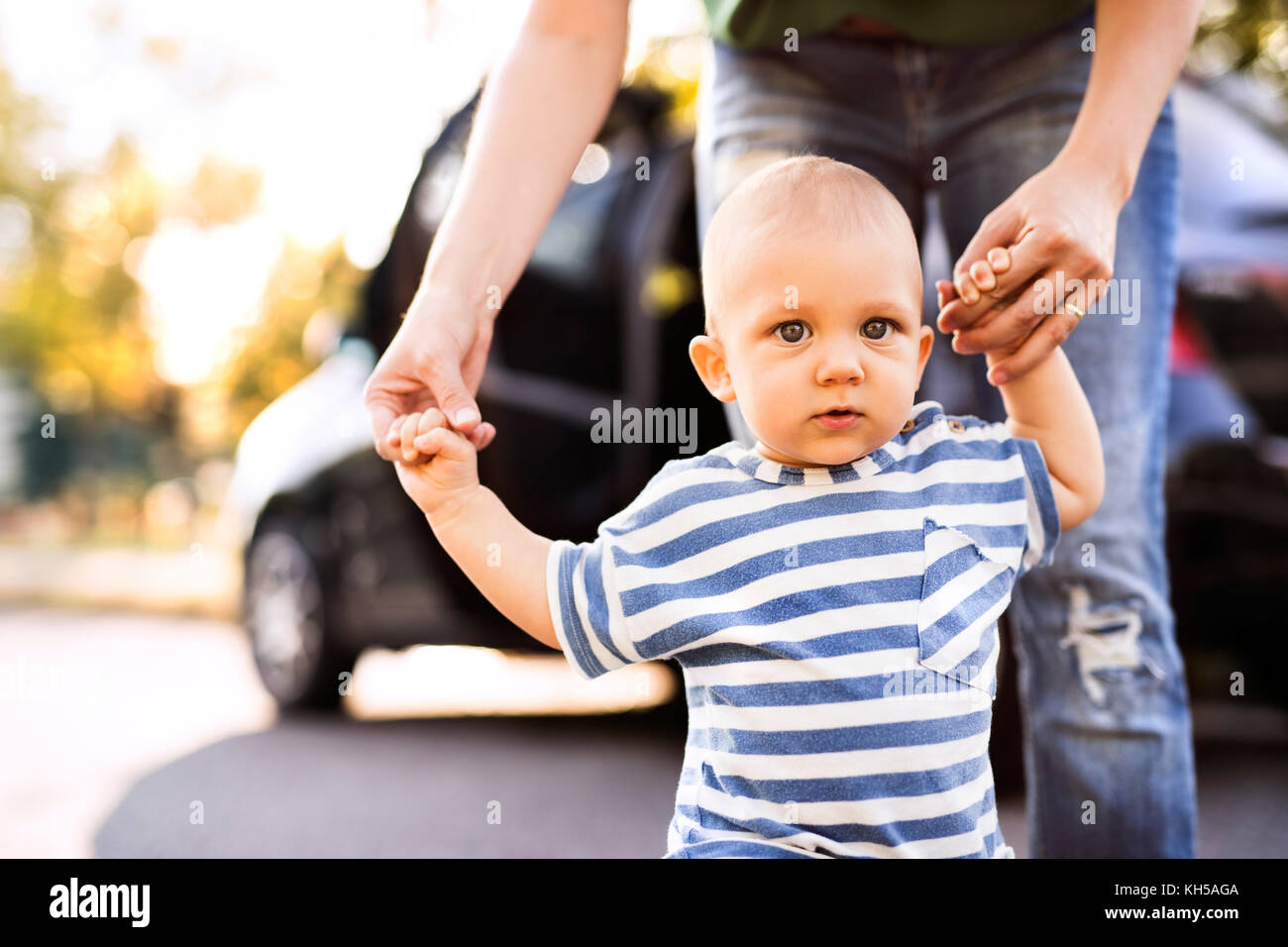 Young mother with her little baby boy walking by the car. Stock Photo