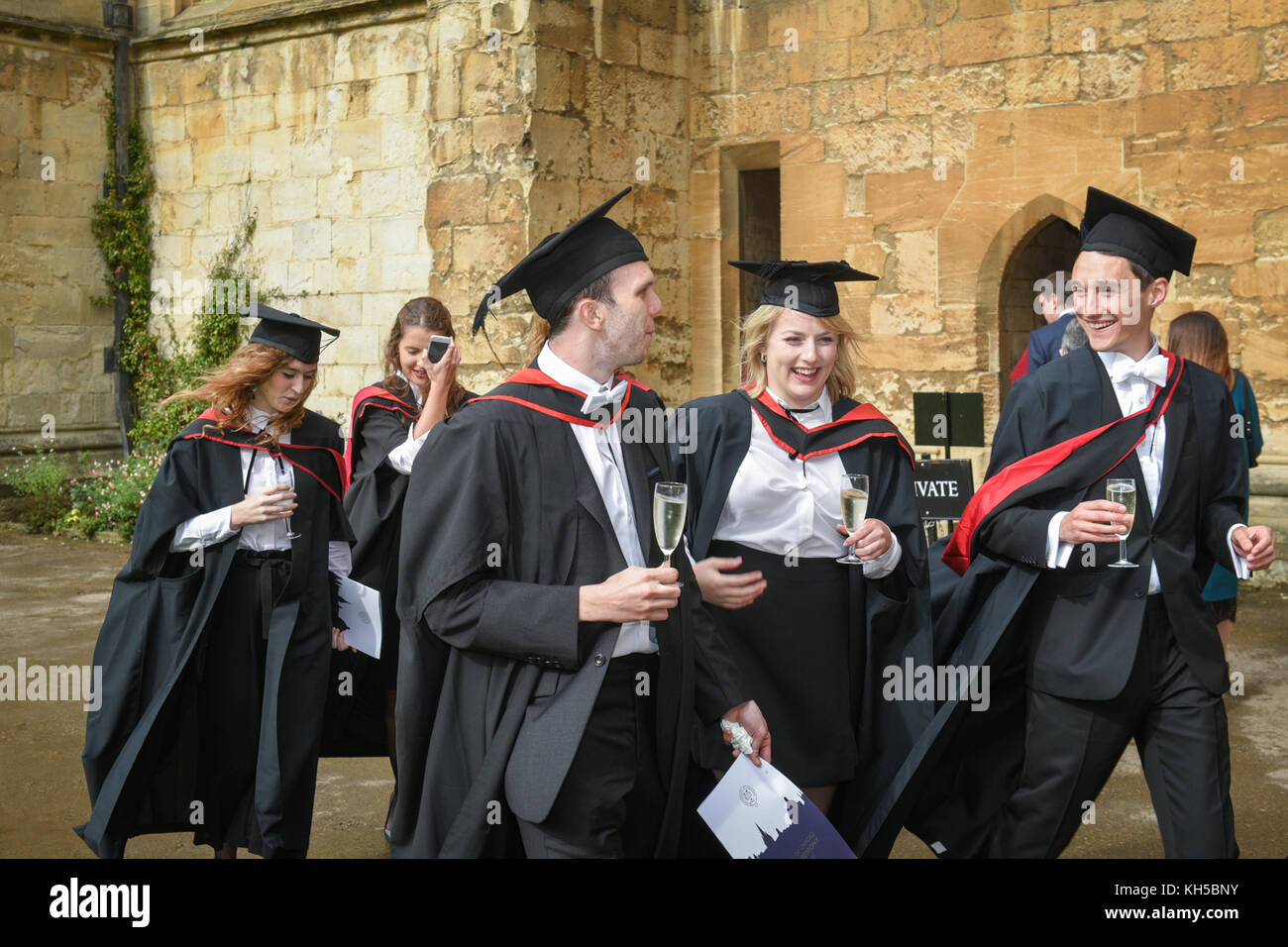Newly graduated Oxford students celebrate with champagne in traditional 'sub fusc' gowns and hats - Stock Image
