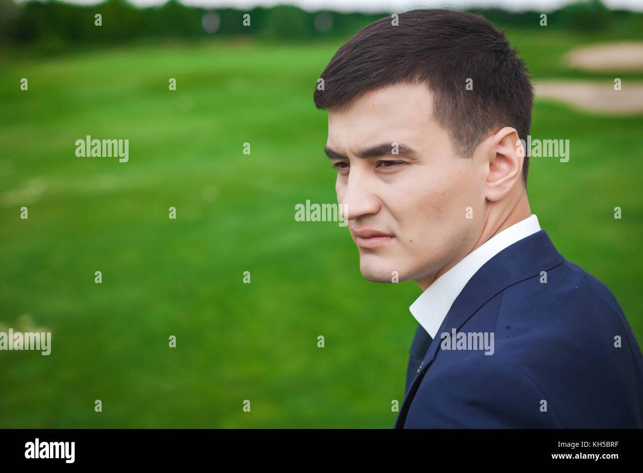Portrait of thoughtfull groom on the green golf field - Stock Image