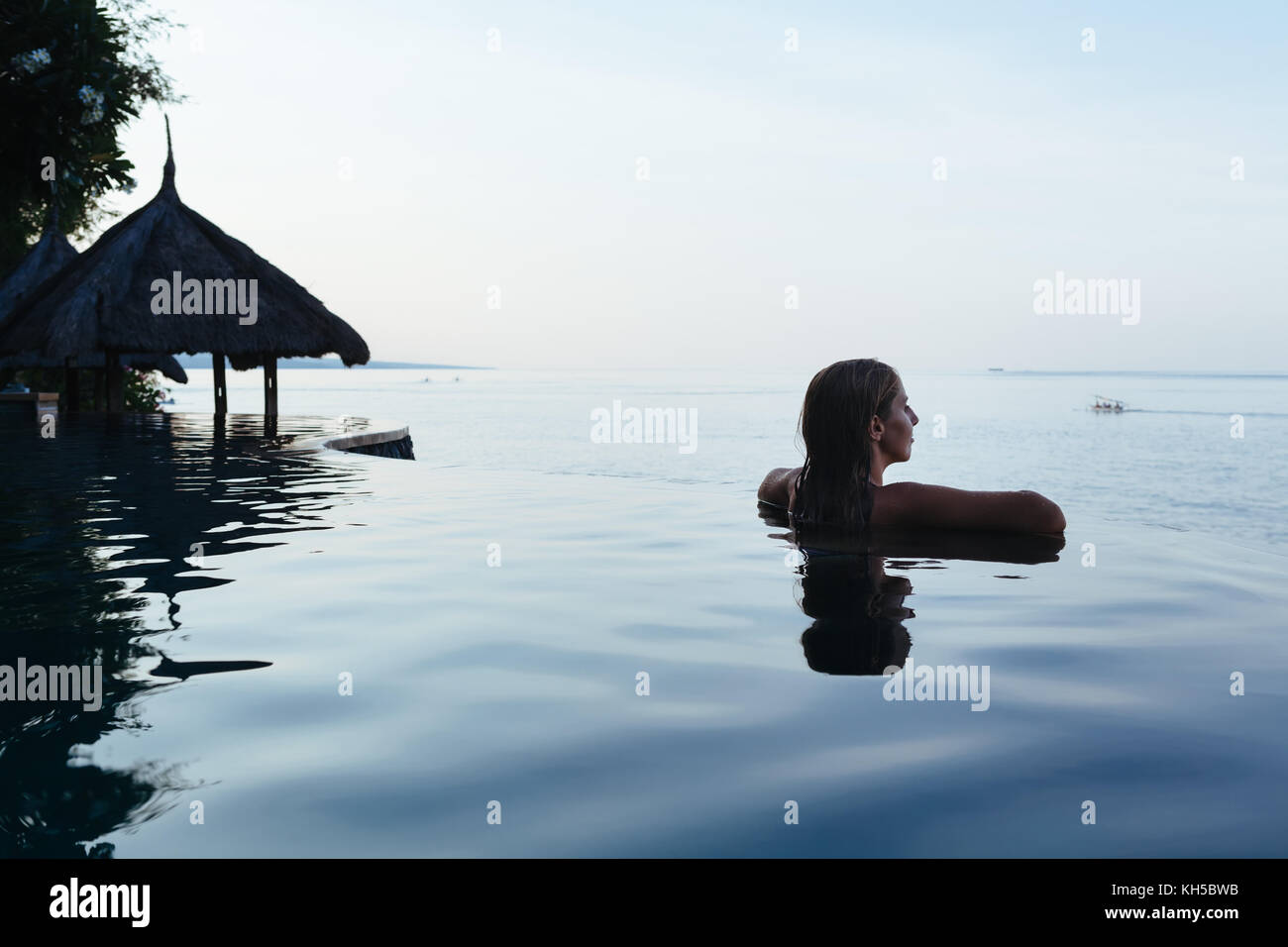 Black silhouette of happy woman on summer beach holiday relaxing in luxury spa hotel in infinity swimming pool with Stock Photo