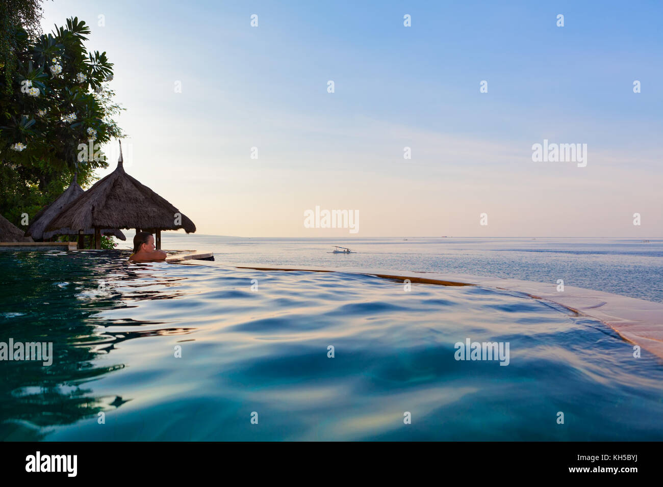 Happy woman on summer beach holiday relaxing in luxury spa resort in infinity swimming pool with colorful sunset Stock Photo
