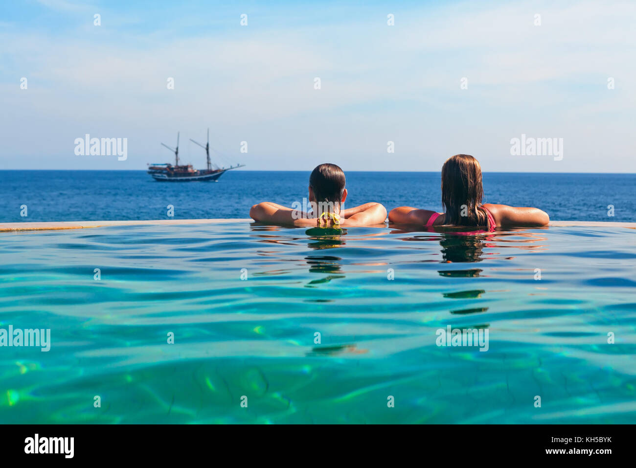 Happy young woman on summer beach holiday relaxing in luxury spa resort in infinity swimming pool with sea view. Stock Photo