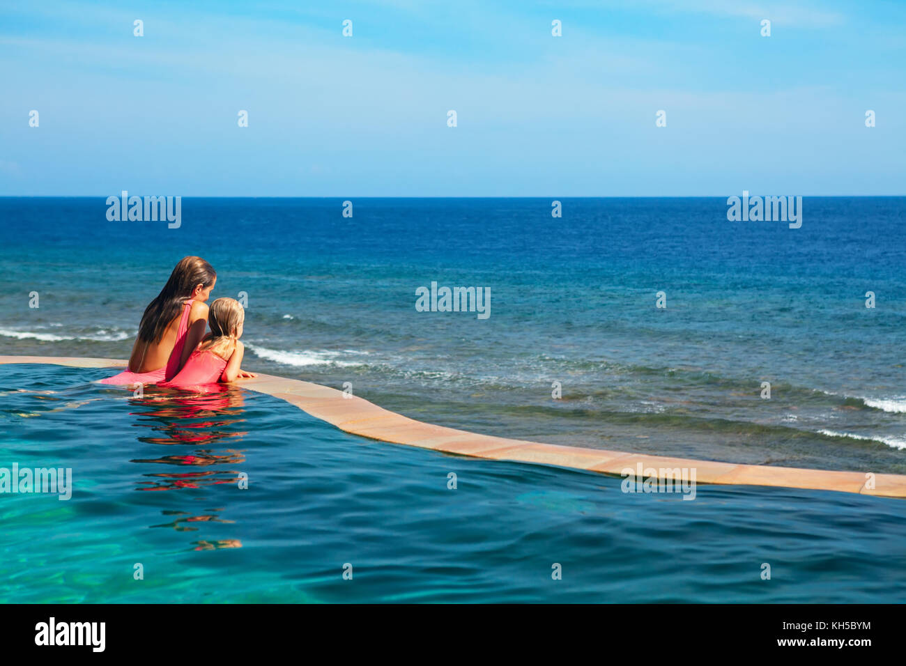 Happy family. Mother, baby relax in luxury spa resort at poolside in infinity swimming pool with sea view. Travel Stock Photo