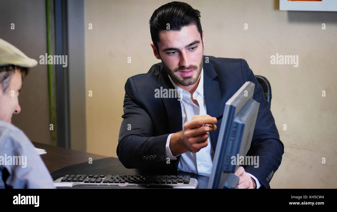 Businessman pointing at monitor screen - Stock Image