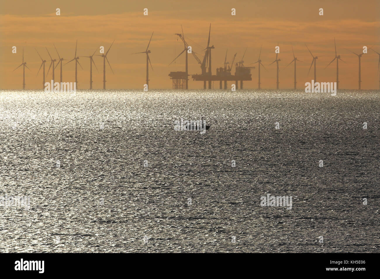 A small fishing boat sails past the giant wind turbines of