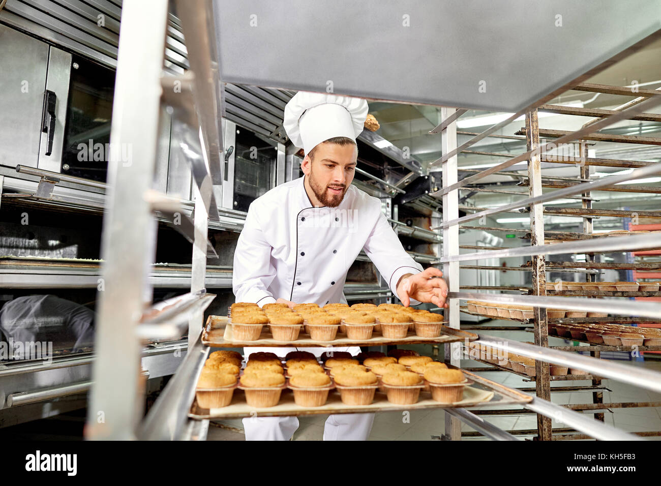 Baker man with a tray of cupcakes in his hands at work in Christ - Stock Image