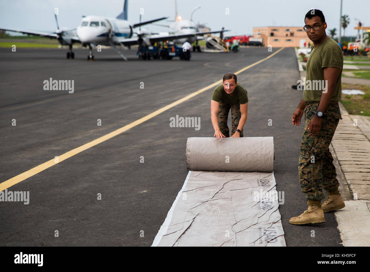 U.S. Marines with Joint Task Force - Leeward Islands unroll a U.S. Agency for International Development tarp as Stock Photo