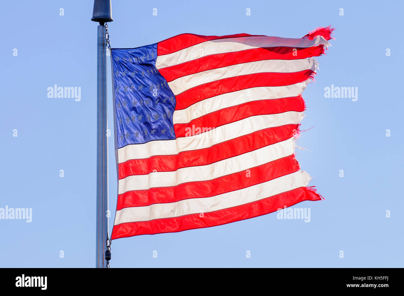 Tattered American flag blowing in the wind - Stock Image