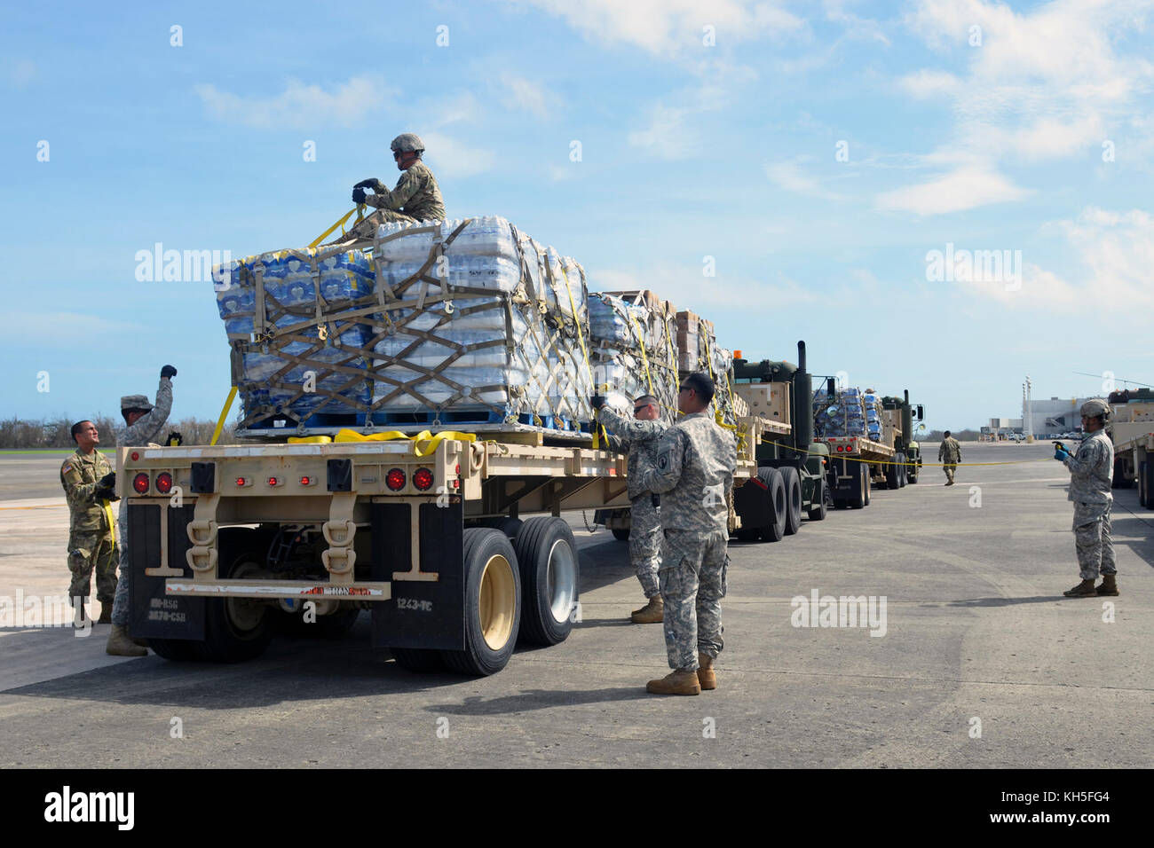 U.S. Army reservists assigned to the 1st Mission Support Command strap down food and water to distribution trucks - Stock Image